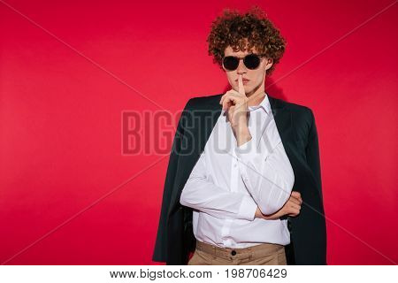 Charming stylish young man in sunglasses and white shirt showing silence gesture with finger over lips isolated over red background