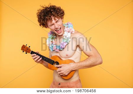 Attractive shirtless man in summer clothes playing ukulele and singing isolated over yellow background