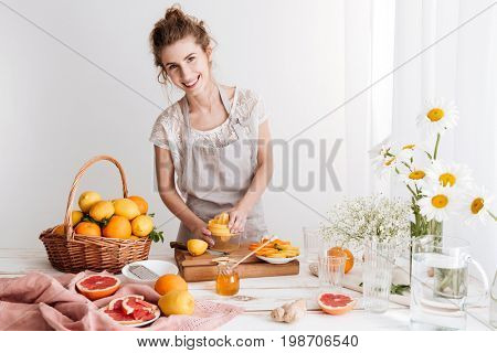 Picture of woman standing indoors and squeezes out juice of a citruses. Looking camera.