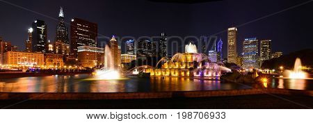 Chicago skyline panorama with skyscrapers and Buckingham fountain at night.