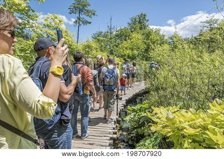 CROATIA PLITVICE, 29 JUNE 2017: Groups of tourists photograph the beauty of the Plitvice Lakes on a summer day.