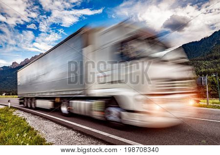 Truck rushes down the highway in the background the Alps. Truck Car in motion blur.