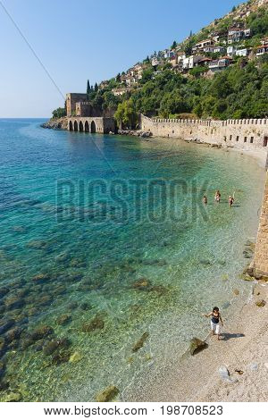 ALANYA TURKEY - JULY 04 2015: Shipyard (Tersane) and the ruins of a medieval fortress (Alanya Castle) on the mountainside.