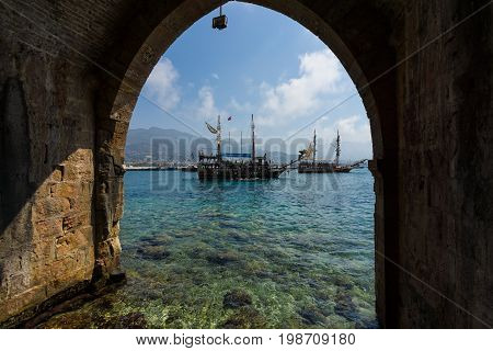 ALANYA TURKEY - JULY 04 2015: Mediterranean Sea. Traditional entertainment resort of Alanya. Sailing aka pirate ships around the fortress of Alanya. View from the shipyard (Tersane) and the ruins of a medieval fortress (Alanya Castle).
