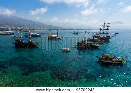 ALANYA TURKEY - JULY 04 2015: Mediterranean Sea. Traditional entertainment resort of Alanya. Sailing aka pirate ships around the fortress of Alanya. View from the bird's-eye view.