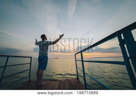 man rises hands up on the lake pier on sunrise