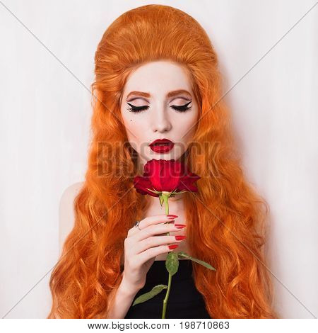 Redead fashionable woman with long hair with unusual appearance in a black fashionable dress with a red rose in hands and arrows on eyes. A vicious fashionable girl with pale skin and closed eyes with long nails. Fashionable retro lady. Fashionable model