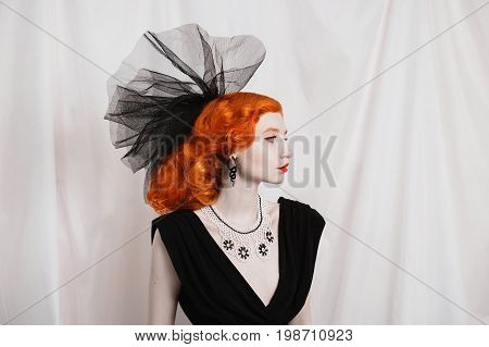 Redhead elegant woman with unusual appearance in black unusual dress and veil on the head and red lips. Unusual elegant girl with pale skin and a beautiful antique unusual necklace on neck and black earrings in the form of snakes. Unusual elegant model.