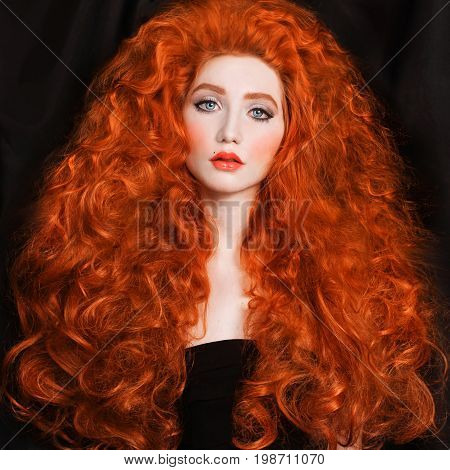 Redhead woman with very long curly hair with unusual appearance in a black dress on a black background. Lovely girl with pale skin with a bright appearance and red curly hair. Lush curly hair. Blue eyes and pink lips. Long curly hair.  Model with long cur