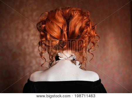 Red-haired woman with beautiful hairstyle standing back. Fashion woman hairstyle. Sophisticated hairstyle. Bright beautiful hairstyle