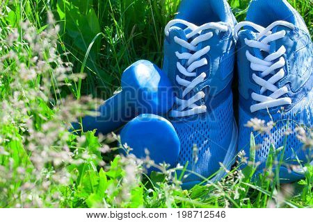 Summer spring outdoor sports composition with blue sneakers and blue dumbbells on green grass background. Concept healthy lifestyle sport and diet in summer spring outdoor running.