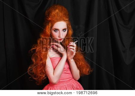 Smoke from a cigarette. Tobacco smoke. A smoking woman with pale skin and long curly red hair in a pink dress on a black background smoke a cigarette. The habit to smoke cigarette. Beautiful girl with red lips with a cigarette in her hands. Beauty makeup.