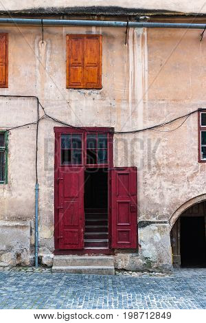 Detail of facade with red door in ancient house in Sibiu city Romania.
