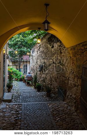 Narrow european medieval street with stone archway in the Sibiu city at Romania.