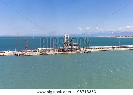 Oil loading and discharge station for tanker ships in a harbor