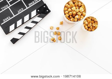 Popcorn for watching fim near clapperboard on white background top view.