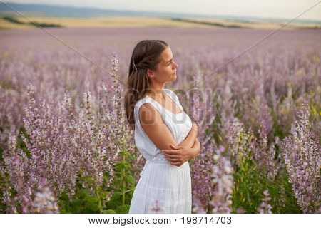 A girl in a white dress is walking through the field of sage