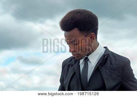 pensive young man suit and tie clouds looking down smart thinking