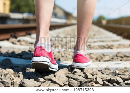 Girl Walking On Rail Road Track In Red Speakers