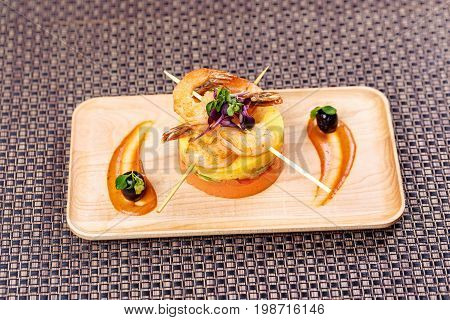 Stir fry shrimp. Fried shrimps with mashed potatoes with sauce on a wooden plate.