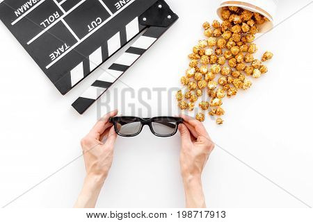To go to the cinema. Clapperboard, glasses and popcorn on white background top view.
