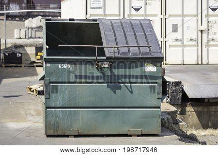 Waste bin located in an alley alongside a building