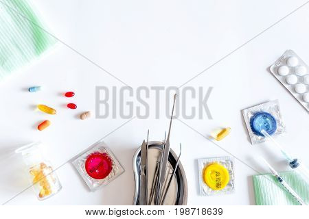 Visit the urologist. Tools and condoms on white background top view.