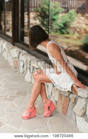 Beautiful Young Woman In White Dress Sitting Alone On Stone Outdoors And Waiting For Someone. Girl P