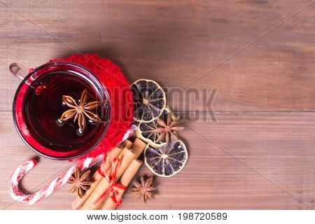 Overhead view of christmas hot drink with citrus and cinnamon over brown wooden background with copy space overhead view