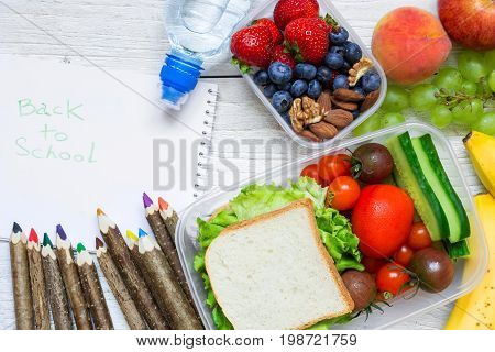 school lunch boxes with sandwich fruits vegetables and bottle of water with colored pencils and back to school inscription. top view. back to school concept