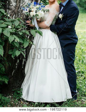 Bride And Groom Hugs In Green Park Near Birch. Groom Hugs Behind The Bride With Wedding Bouquet Of P