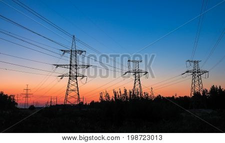 High voltage power lines during fiery sunrise