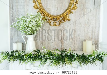 White decorative fireplace with candles on it near wooden wall. Floral decoration of white flowers and greenery over white fireplace