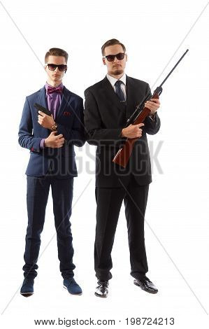 Two men wearing suits and sunglasses holding guns
