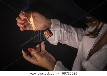 Womens hands ignite big matches for a tompus cigare or a fireplace. Studio shoot