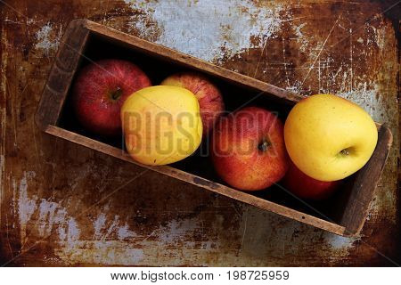 Red and yellow apples in a vintage wood box against tarnished metal background.