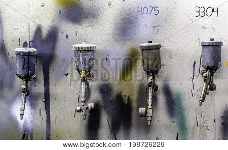 Four airbrushes for car painting on a white wall with different colors of paint
