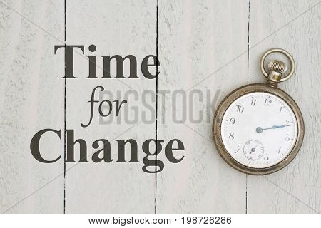 Time for Change message with retro silver pocket watch on weathered wood