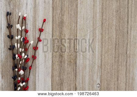 Red white and blue pip floral berry spray on weathered wood background with copy space for your message