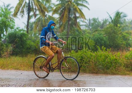 Kampot, Cambodia - December 14, 2016: Young Asian person (unidentified) who wears a face mask rides a rusty bicycle while heavy raining. Rain drops are seen