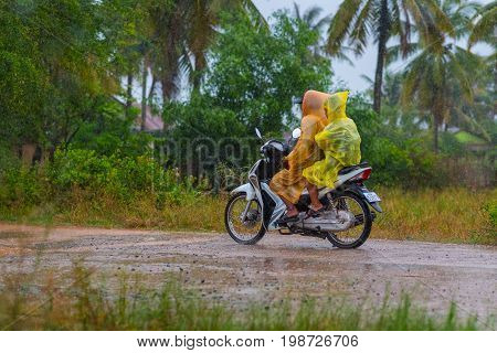 Kampot, Cambodia - December 14, 2016: Two people (unidentified) in packable plastic raincoats ride scooter on dirt road while heavy raining. Drops, palm trees seen.