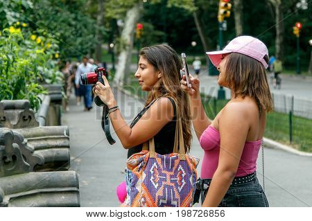 New York August 3 2017: Two unidentified young ladies are taking pictures of a girl (not pictured) in Central Park.