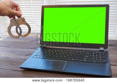 Man Holding Handcuffs Near Laptop