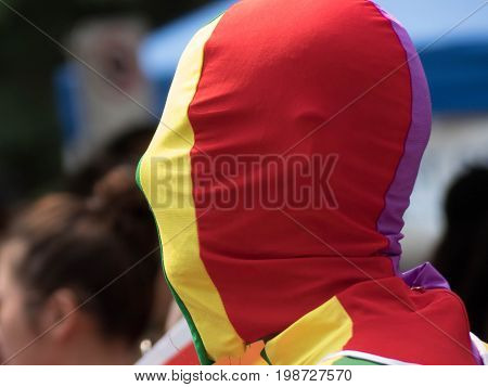 Concept coming out face closed by rainbow flag closeup background