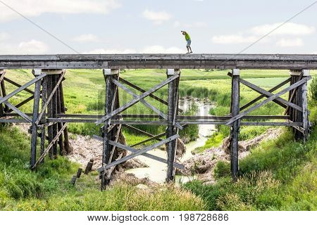 horizontal image of a caucasian man taking a risk and walking on the edge of a very tall  old abandoned railroad track with a stream flowing underneath with green vegetation in the summer time.