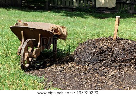 Old Wooden Wheelbarrow Next To A Large Pile Of Manure