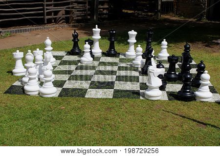 Giant game of chess with board laid out on grass outside