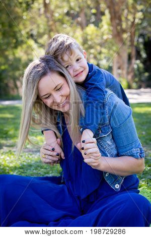 Mother And Young Son Having Fun Sharing Time Together Whilst Sitting On Beautiful Day Outdoors