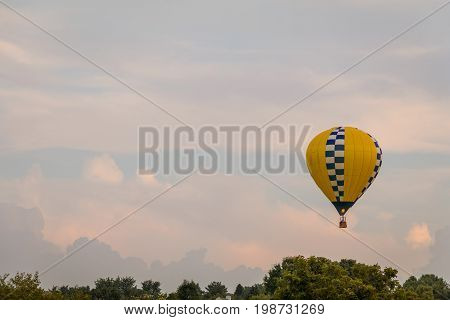 Yellow and blue patterned hot air balloon floats among the mountains in a beautiful sky at dusk