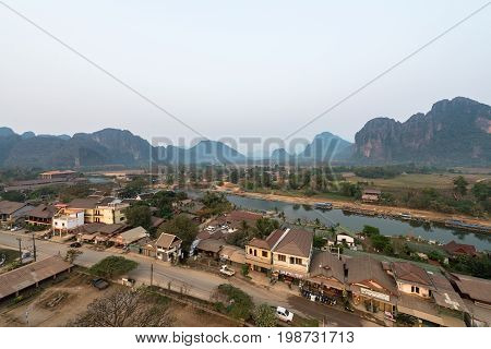 VANG VIENG LAOS - MARCH 15 2017: Panorama picture of Nam Song River with tropical vegetation and houses in Vang Vieng from the top inside the balloon in Laos during sunrise time.